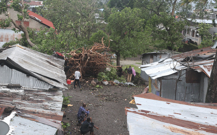 People stand by damaged houses and fallen trees on April 25, 2019 in Moroni after tropical storm Kenneth hit Comoros before heading to recently cyclone-ravaged Mozambique. Picture: AFP