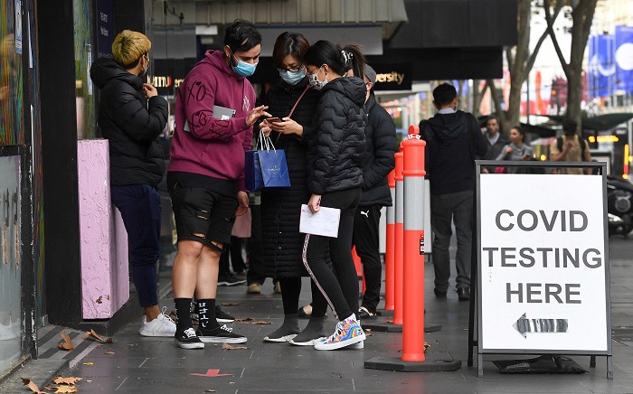 FILE: People queue at a COVID-19 testing station in Melbourne on 25 May 2021, as the city recorded five new locally-acquired coronavirus cases in the community after an 85-day unbroken stretch of zero infections. Picture: William West / AFP