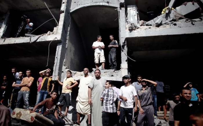 Palestinians gather on the rubble and shell of a building destroyed following an Israeli military strike, as they watch rescuers working in Rafah in the south of the Gaza Strip, on 21 August 2014. Picture: AFP