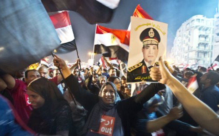 People celebrate at Tahrir Square with a portrait of Army chief Abdel Fattah al-Sisi after a broadcast confirming that the army will temporarily be taking over from the country's first democratically elected president Mohamed Morsi on3 July,2013 in Cairo. Picture: AFP/Khaled Desouki