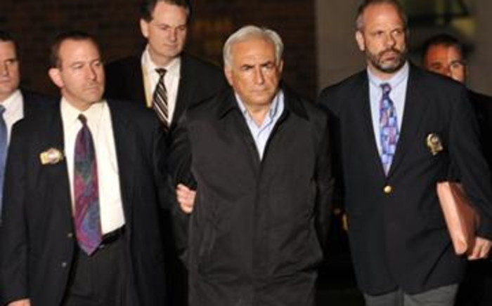IMF head Dominique Strauss-Kahn (C) is taken out of a police station in New York on May 15, 2011 after he was charged with attempting to rape. Picture: AFP.