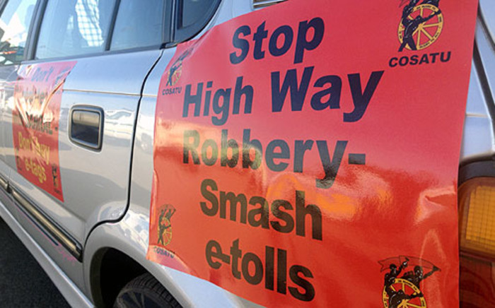 Cosatu members prepare for the drive-slow protest by attaching anti-e-toll banners onto their cars. Picture: Christa van der Walt/EWN