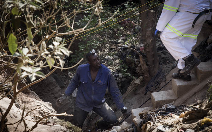 FILE: A Zama Zama (illegal miner) pulls an injured miner, whose hand is seen at left, out the entrance disused Langlaagte gold mine shaft entrance on 11 September 2016 in Johannesburg. Picture: AFP