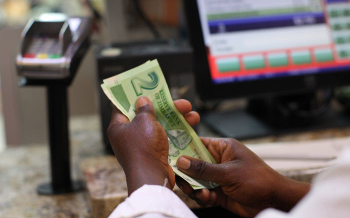 FILE: A man holds bond notes released by the Reserve Bank of Zimbabwe in Harare central business centre on 28 November 2016. Picture: AFP