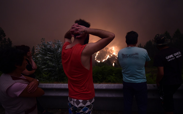 Villagers look at flames during a wildfire near the village of Mega Fundeira on 18 June, 2017. Picture: AFP