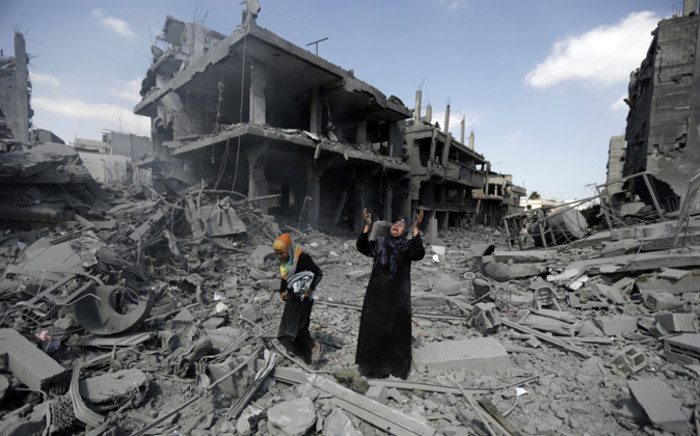 A Palestinian woman pauses amid destroyed buildings in the northern district of Beit Hanun in the Gaza Strip during a humanitarian truce on 26 July, 2014.