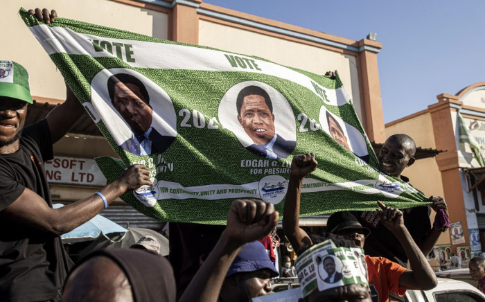 Supporters of the ruling Patriotic Front of the incumbent President Edgar Lungu wave a flag showing a portrait of Lungu during a campaign parade in Lusaka, on 10 August 2021. Zambians will decide on 12 August 2021, whether to re-elect President Edgar Lungu after the country's worst economic performance in decades and a crackdown on dissent that has raised fears of unrest in the southern African country. Picture: Patrick Meinhardt/AFP