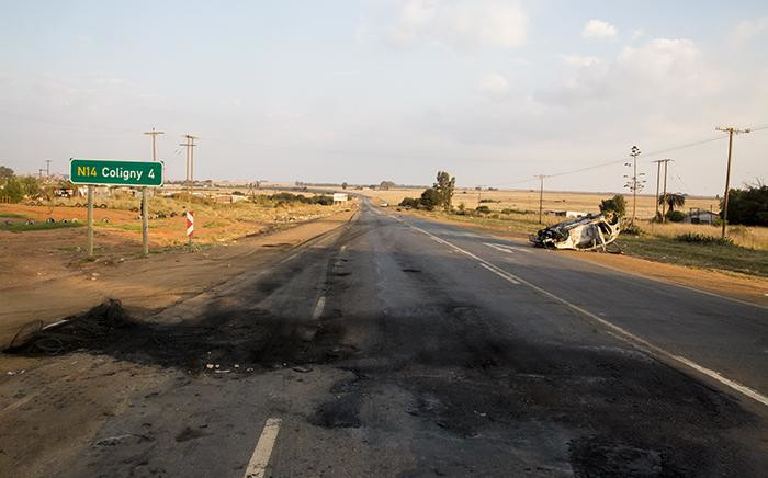 FILE: The wreckage of a vehicle which was set alight lies next to the road just outside of Coligny in the North West following protests in the area over the death of a young boy. Picture: Reinart Toerien/EWN.