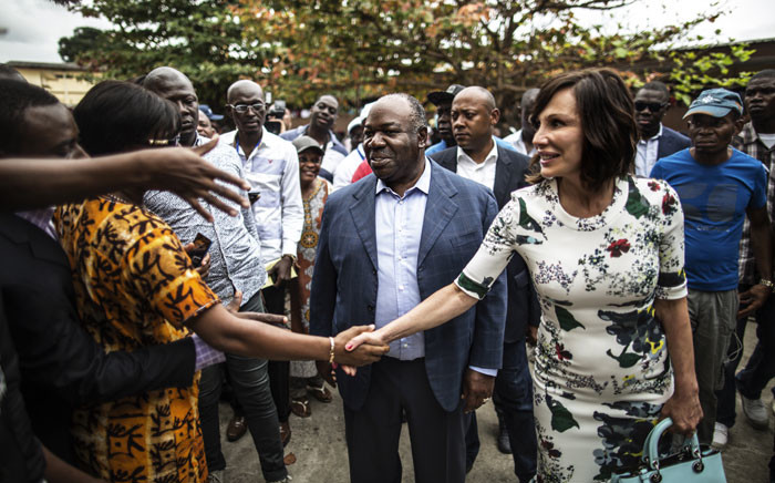 Gabonese President Ali Bongo Ondimba and his wife Sylvia greet supporters after casting their vote at a polling station during the presidential election on 27 August 2016 in Libreville. Picture: AFP.