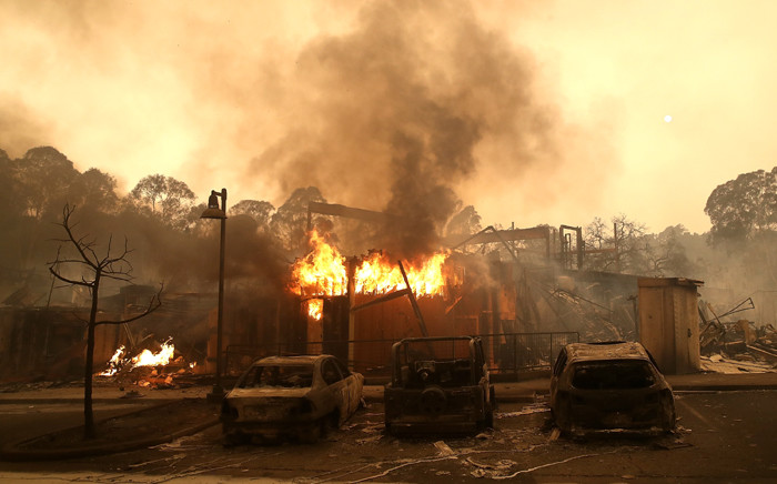 FILE: Burned out cars sit next to a building in a fire-ravaged neighbourhood on 9 October 2017 in Santa Rosa, California. Picture: AFP.