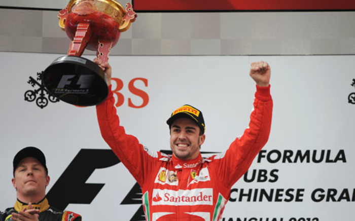 Ferrari driver Fernando Alonso of Spain (C) holds up the trophy as he celebrates after winning the Formula One Chinese Grand Prix with in Shanghai on April 14, 2013. Picture: AFP