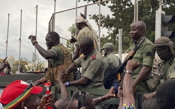 Malian soldiers are celebrated as they arrive at the Indipendence square in Bamako on 18 August 2020. Mali's Prime Minister Boubou Cisse called on 18 August 2020, for 'fraternal dialogue' with soldiers who seized a key military garrison and have triggered fears of a coup attempt. Picture: AFP.