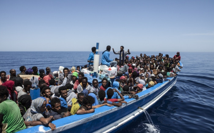 FILE: A handout picture taken on 3 May, 2015 released by the MOAS (Migrant Offshore Aid Station) shows migrants aboard a wooden boat on the Mediterranean sea. Picture: AFP.