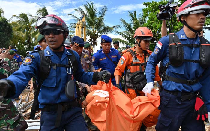 FILE: Members of an Indonesian search and rescue team carry a body bag taken from the Villa Stephanie accommodation in Carita in Banten province on 24 December 2018. Picture: AFP.