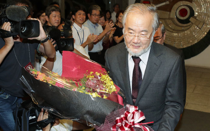 Yoshinori Ohsumi receives a bouquet of flowers at the Tokyo Institute of Technology in Tokyo on October 3, 2016 after winning the Nobel Prize in Medicine. Picture: AFP