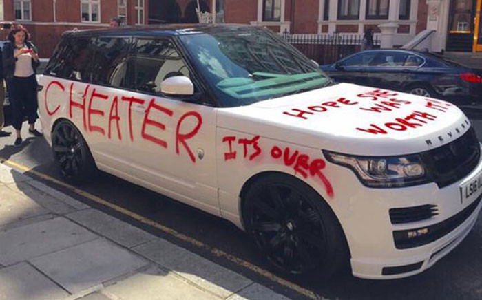 A luxury car spray painted with graffiti has drawn large crowds outside one of London's most famous stores. Picture: Twitter.