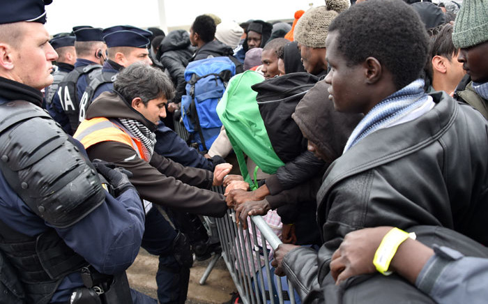 "French riot police hold back migrants as they clear the ""Jungle"" migrant camp in Calais. Picture: AFP"
