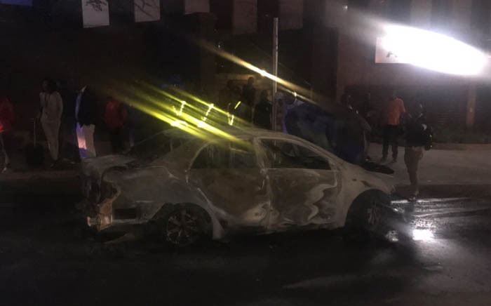 People stand next to one of the Uber cars that were torched near the Gautrain Station in Sandton. Picture: Clement Manyathela/EWN.