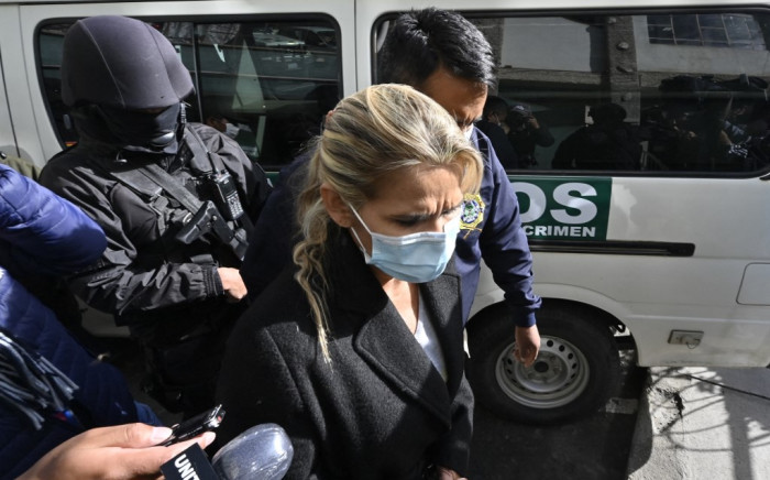 Former interim Bolivia's President Jeanine Anez (C) is escorted by police members of the Special Force against Crime (FELCC) on 13 March 2021, after being arrested in La Paz. The Bolivian judiciary ordered on 19 March 19 the transfer to a clinic of former interim President Jeanine Anez,ffering from health problems, after she was imprisoned. Picture AFP