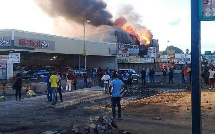 People watch a shop burn after it was torched in the Rustenburg CBD on 10 January, 2018. Residents allegedly attacked alleged drug dens in the area. Picture: Supplied