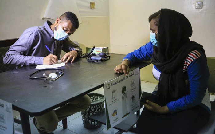 FILE: A woman consults a doctor at a small treatment centre set up by local volunteers in the Shambat district of northern Khartoum on 18 June 2020, amid acute shortage of medicine as Sudan fights to control the spread of COVID-19 coronavirus. Picture: AFP