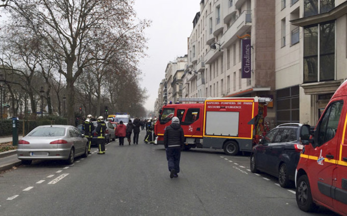Firefighters and rescue services gather near the offices of the French satirical newspaper Charlie Hebdo in Paris on 7 January, 2015, after armed gunmen stormed the offices leaving eleven dead, including two police officers, according to sources close to the investigation. Picture: AFP.