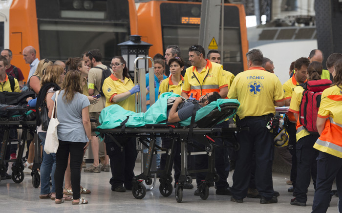A man lies on a stretcher as emergency personnel gather on a platform beside a train at Estacio de Franca (Franca station) in central Barcelona on 28 July, 2017 after the regional train appears to have hit the end of the track inside the station injuring at least 23 people. Picture: AFP.