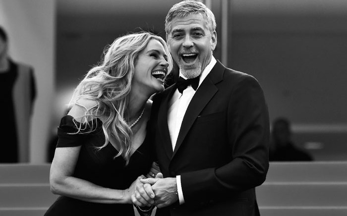 """US actress Julia Roberts laughs on 12 May 2016 with US actor George Clooney as they arrive for the screening of the film """"Money Monster"""" at the 69th Cannes Film Festival in Cannes, southern France. Picture: AFP/LOIC VENANCE"""