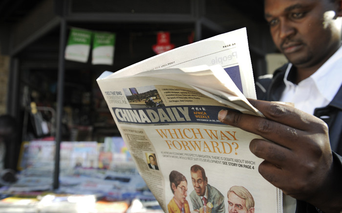 FILE: A newspaper consumer reads a copy of China Daily's Africa edition of its daily newspaper in front of a newsstand in the Kenyan capital in December 2012. Picture: AFP.