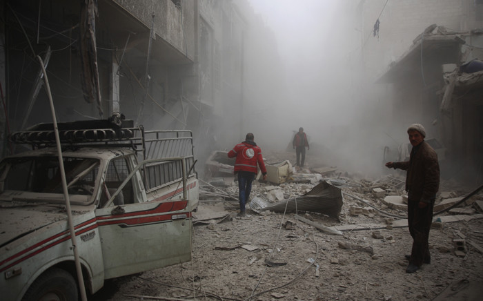 FILE: Members of the Syrian Arab Red Crescent search for survivors amid the rubble of destroyed buildings following air strikes in the rebel-held town of Douma. Picture: AFP.