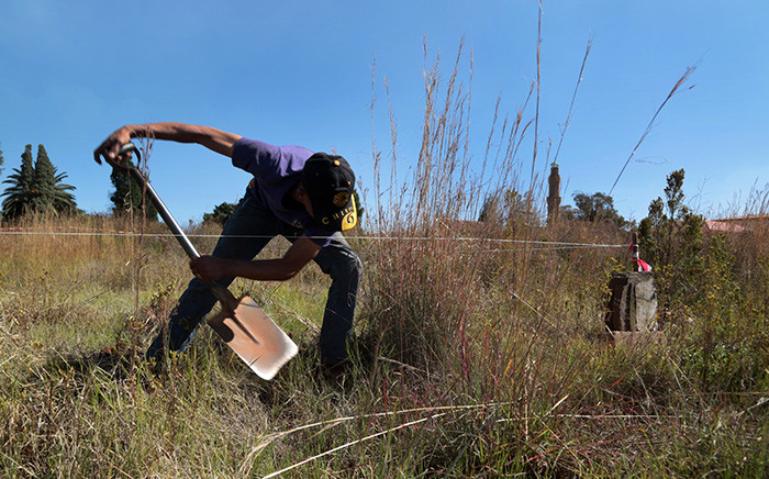 Eldorado Park resident Dawid Stevenson clears a vacant plot of land where he plans to build his home. Picture: Vumani Mkhize/EWN