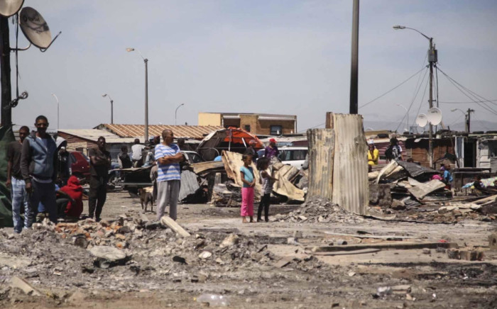 FILE: Residents from an informal settlement, clean up after a shack fire. Picture: Cindy Archillies/EWN
