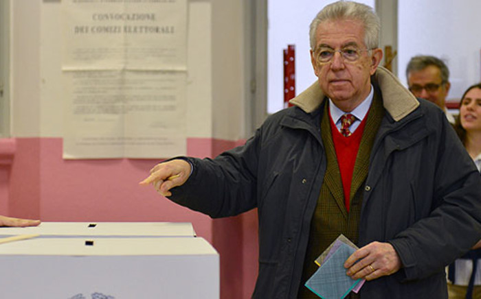 Italy's outgoing Prime Minister Mario Monti prepares to cast his ballot in a polling station on 24 February 2013 in Milan. Picture: AFP