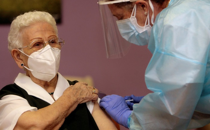 Araceli Hidalgo, 96, a resident of Los Olmos nursing home for the elderly, receives a first dose of the Pfizer-BioNTech COVID-19 vaccine on 27 December 2020, in Guadalajara, becoming the first person vaccinated against coronavirus in Spain. Picture: AFP.