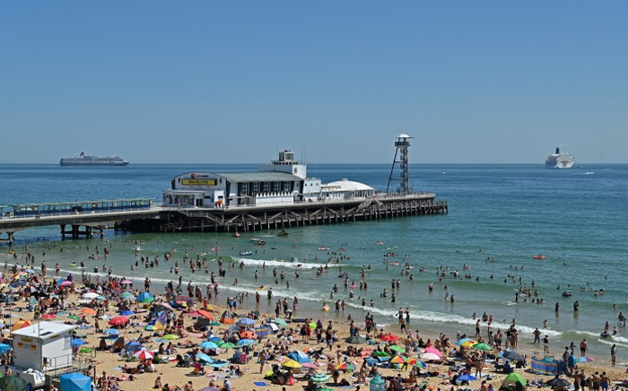 Beachgoers enjoy the sunshine as they sunbathe and play in the sea, backdropped by moored cruise ships, on Bournemouth beach in Bournemouth, southern England, on 25 June 2020. Picture: AFP.