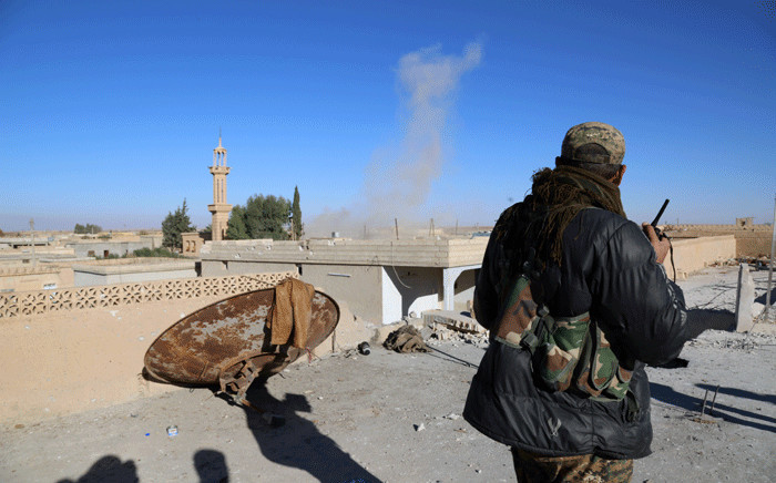 FILE: A commander from the Kurdish-Arab alliance, known as the Syrian Democratic Forces, watches as a mine explodes in the distace, from the roof of a building in the village of Tal Saman, 25km from IS's de facto Syrian capital of Raqa, on 19 November 2016. Picture: AFP.