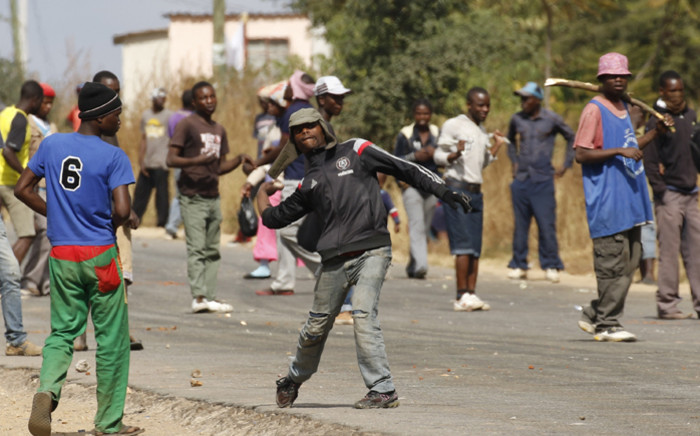 Protesters hurl stones in Harare on 4 July, 2016 during clashes with Zimbabwe's riot police. Picture; AFP.