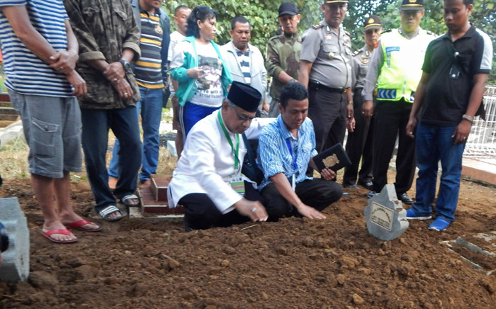 An Islamic cleric (L) prays with Iwan Setiawan (R), brother of executed Indonesian drug convict Zainal Abidin following his burial at a cemetery in Cilacap on 29 April, 2015. Eight drug convicts including two Australians Andrew Chan and Myuran Sukumaran were executed by firing squad on 29 April on the high-security prison island of Nusakambangan in central Indonesia, but a Filipina was spared at the 11th hour. Picture: AFP.