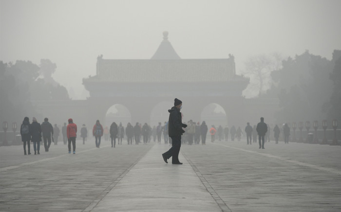 FILE: An elderly man walks in front of a group of people during heavy smog at the Temple of Heaven park in Beijing. Picture: AFP.