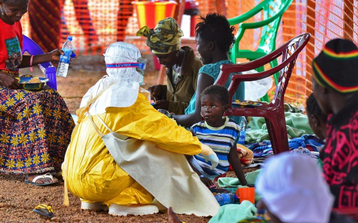 FILE:An MSF medical worker feeds an Ebola child victim at an MSF facility in Kailahun, on 15 August, 2014. Picture: AFP.