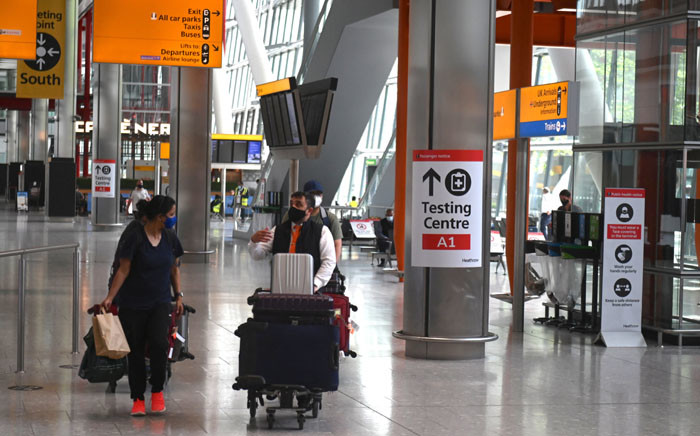 Passengers push their luggage past signage displaying the way to a COVID-19 test centre, in Terminal 5 at Heathrow airport in London, on 3 June 2021. Picture: DANIEL LEAL-OLIVAS/AFP