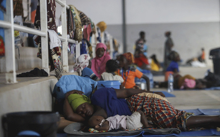 In this file photo taken on 2 April 2021, a woman rests with her baby on the ground at the Pemba Sports center that is now a shelter in Pemba. On 24 March 2021 armed groups terrorised the port in the poor but gas-rich Cabo Delgado region, killing at least dozens of people.  Picture: Alfredo Zuniga/AFP.