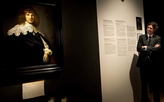 Amsterdam art dealer and historian Jan Six (R) stands beside 'Portrait of a Young Gentleman' by Rembrandt van Rijn in The Hermitage Museum, Amsterdam on 16 May 2018. Picture: AFP.