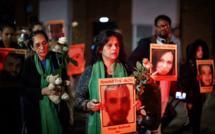 Families and friends who lost loved ones in the Grenfell Tower fire hold portraits of victims as they march to Grenfell Tower in west London at midnight 14 June 2018 to honour the 71 people who died when a fire ripped through the Grenfell tower block in London one year ago. Picture: AFP