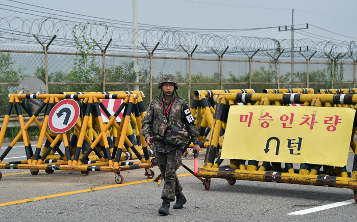 A South Korean soldier walks by barricades on the road leading to North Korea's Kaesong joint industrial complex at a military checkpoint in the border city of Paju on 21 August, 2015. Picture: AFP.