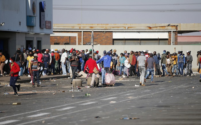 FILE: People carry goods as they loot and vandalise the Lotsoho Mall in Katlehong township, East of Johannesburg, on 12 July 2021. Several shops are damaged and cars burnt in Johannesburg, following a night of violence. Police are on the scene trying to control further protests. It is unclear if this is linked to sporadic protests following the incarceration of former president Jacob Zuma. Picture: Phill Magakoe / AFP