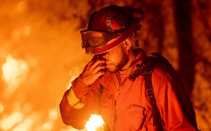 FILE: An inmate firefighter pauses during a firing operation in Redding, California on 27 July 2018.  The blaze on 28 October 2019, the largest of more than a dozen wildfires burning throughout the state, has destroyed dozens of homes and vineyards, including the renowned 150-year-old Soda Rock Winery. Picture: AFP.