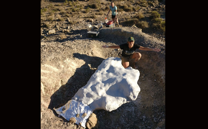A scientist Kimi Chapelle and a dinosaur bone with a protective layer of plaster in Sterkspruit. Picture: Supplied.
