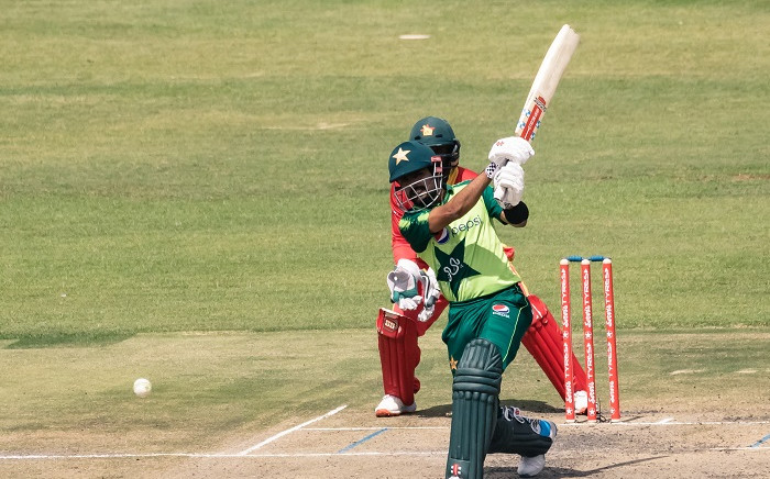 Pakistan's Babar Azam plays a shot as wicket keeper Regis Chakabva looks on during the third Twenty20 international cricket match between Zimbabwe and Pakistan at the Harare Sports Club in Harare on April 25, 2021. Picture: Jekesai Njikizana / AFP