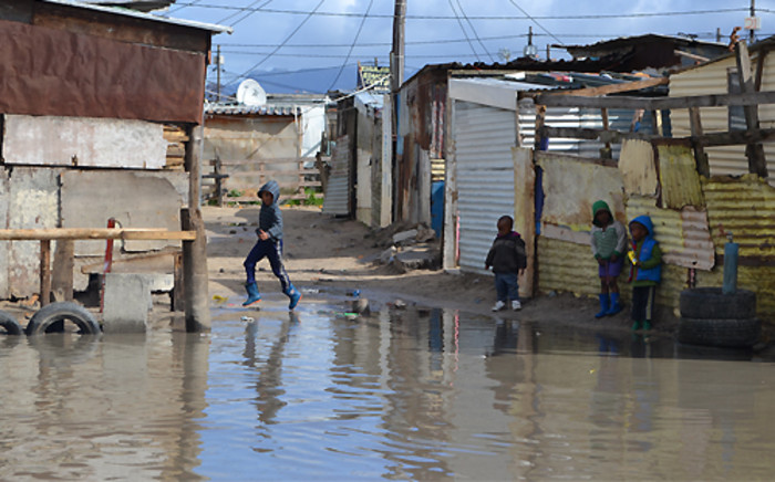 """Children play in a flooded street in Kosovo informal settlement in Cape Town after heavy rain in August 2013. Picture: Aletta Gardner/EWN"